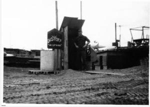 """3. Ο Σμηναγός Ρόμπερτ Ρόμπσον στέκεται έξω από την είσοδο του υπόγειου στρατώνα και καταφύγιου του """"Ξεσκονίσματος"""" στη Ζώνη Προσγείωσης Χωκ Χιλ λίγους μήνες πριν την αποστολή διάσωσης του καταρριφθέντος πληρώματος στο Χίεπ Ντουκ. (Η φωτογραφία είναι ευγενική παροχή του Ρόμπερτ Μ. Ρόμπσον)"""
